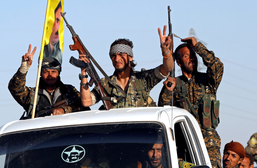 Fighters of Syrian Democratic Forces make the V-sign as their convoy passes in Ain Issa, Syria. (photo credit: REUTERS)