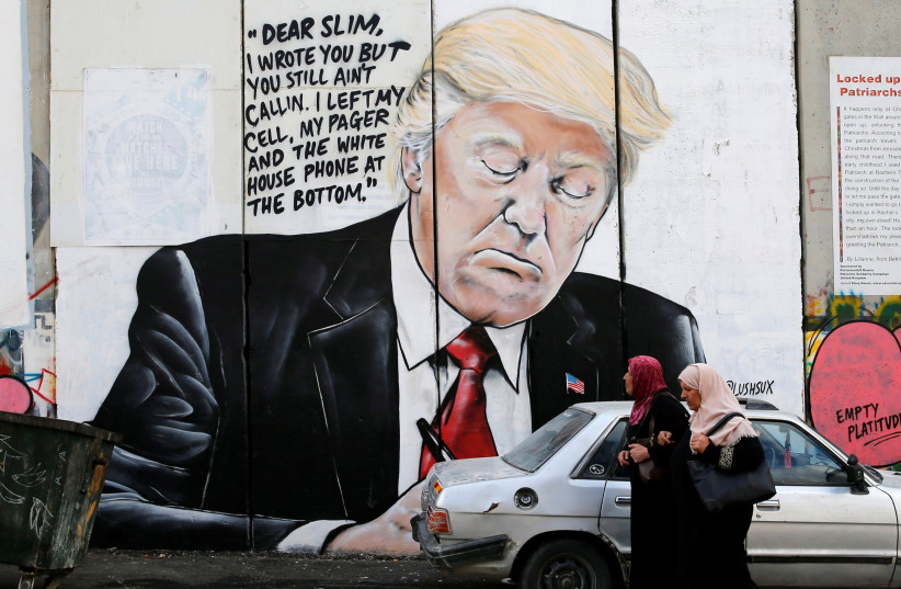 Palestinian women walk by a mural of Donald Trump on the West Bank separation wall, October 2017 (photo credit: AMMAR AWAD / REUTERS)