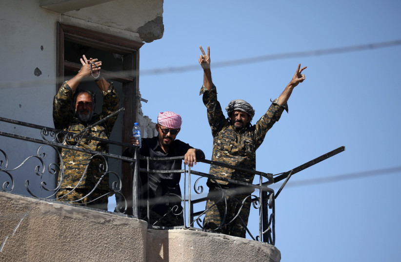 """Fighters of Syrian Democratic Forces gesture the """"V"""" sign at the frontline in Raqqa, Syria October 16, 2017.  (photo credit: REUTERS)"""
