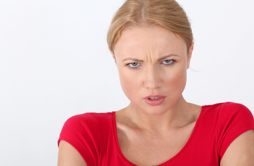 Woman in red shirt with angry look (photo credit: INGIMAGE PHOTOS)