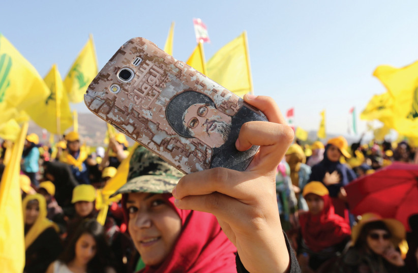 A HEZBOLLAH supporter shows off a picture of leader Sayyed Hassan Nasrallah on her phone during a rally marking the 10th anniversary of the end of Hezbollah's 2006 war with Israel, in Bint Jbeil, southern Lebanon (photo credit: REUTERS)