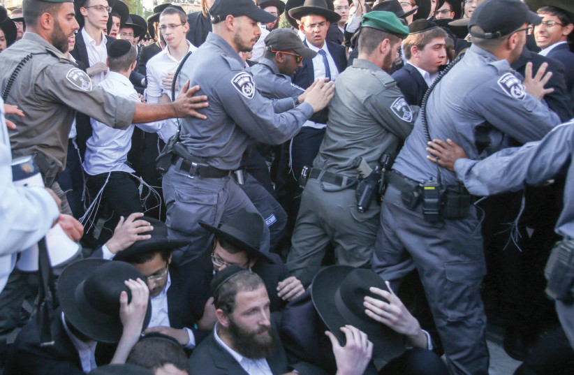 Police clear opponents of of IDF service from the tracks near the Jerusalem Light Rail's Haturim Station yesterday. (photo credit: MARC ISRAEL SELLEM/THE JERUSALEM POST)