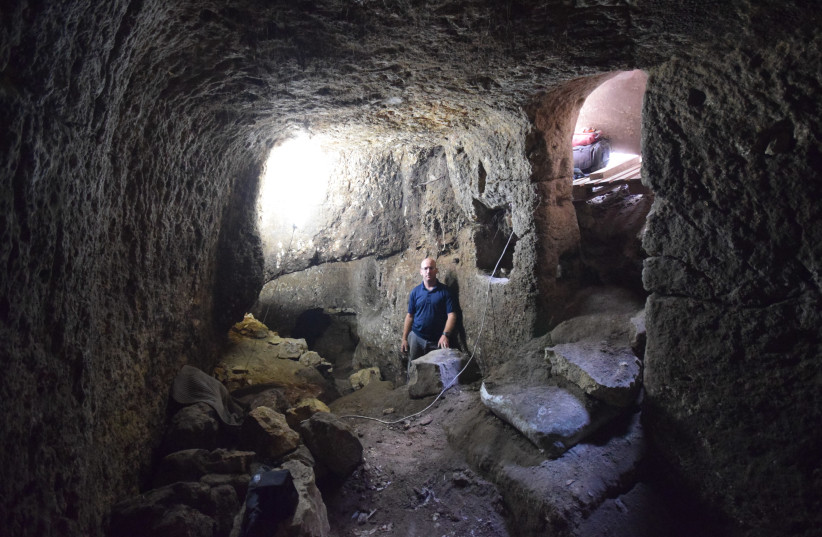 An inspector from the Antiquities Authority inside the plundered caves. (photo credit: COURTESY OF IAA)