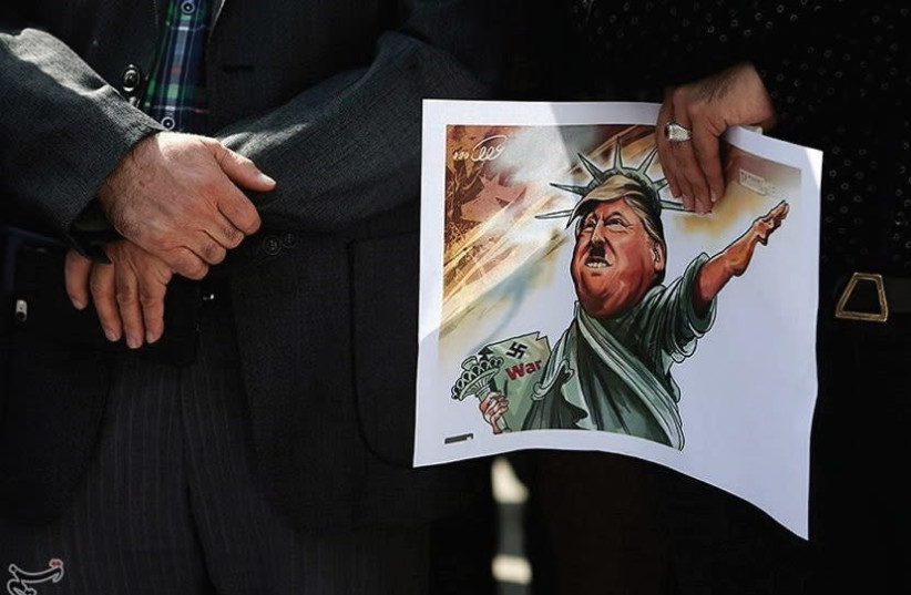 An Iranian student holds a caricature of US President Donald Trump during a protest against Trump's latest speech on Iran, in Tehran. (photo credit: REUTERS)