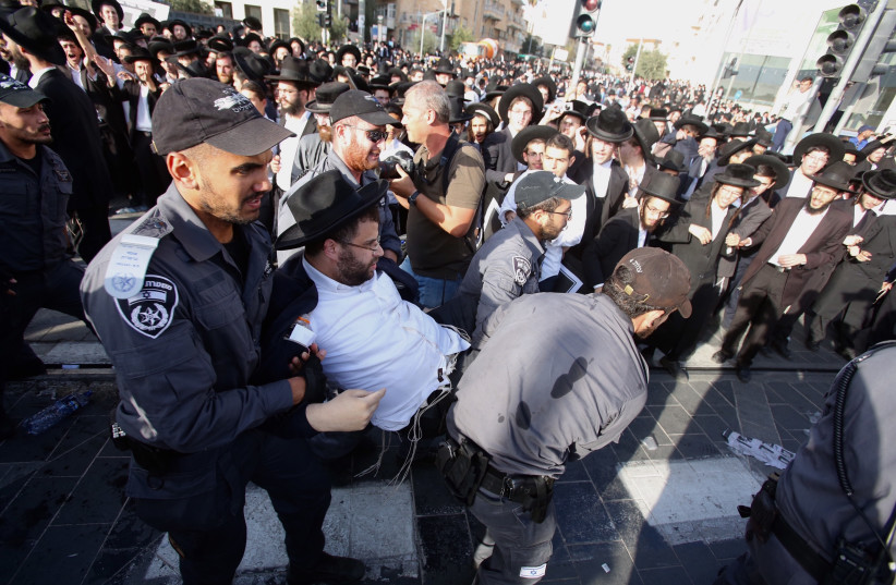 Police arrest a haredi man protesting against the drafting of ultra-Orthodox into the IDF, October 2017 (photo credit: MARC ISRAEL SELLEM/THE JERUSALEM POST)