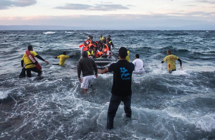 IsraAID Greeting Syrian refugees on a Greek beach. (photo credit: MICKEY NOAM-ALON / ISRAAID)