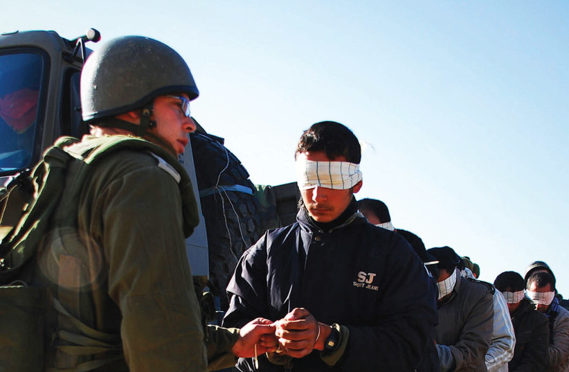 An IDF soldier stands next to a blindfolded Palestinian prisoner (photo credit: REUTERS/IDF HANDOUT)