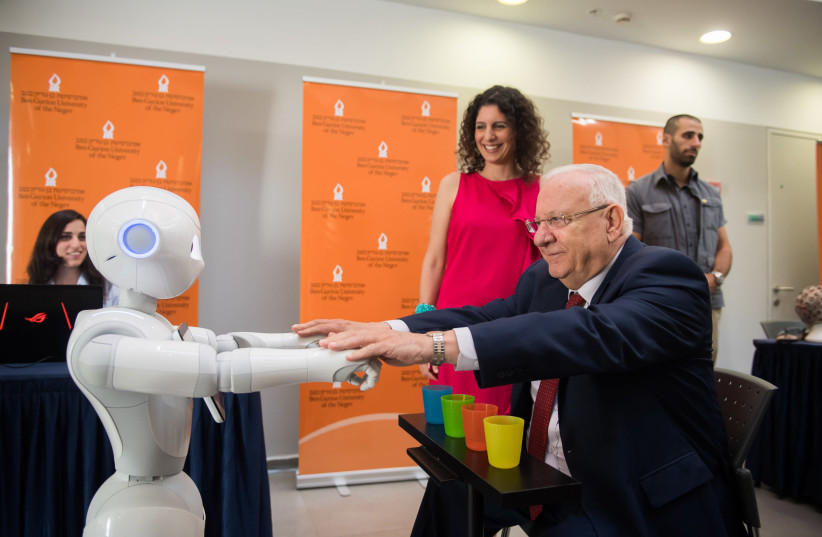 Dr. Shelly Levy-Tzedek (in red dress) demonstrates to President Rivlin how she uses robots for physical therapy during the president's visit to BGU. Lab Engineer Avital Elishay (at the computer) is running the demonstration. (photo credit: DANI MACHLIS/BGU)