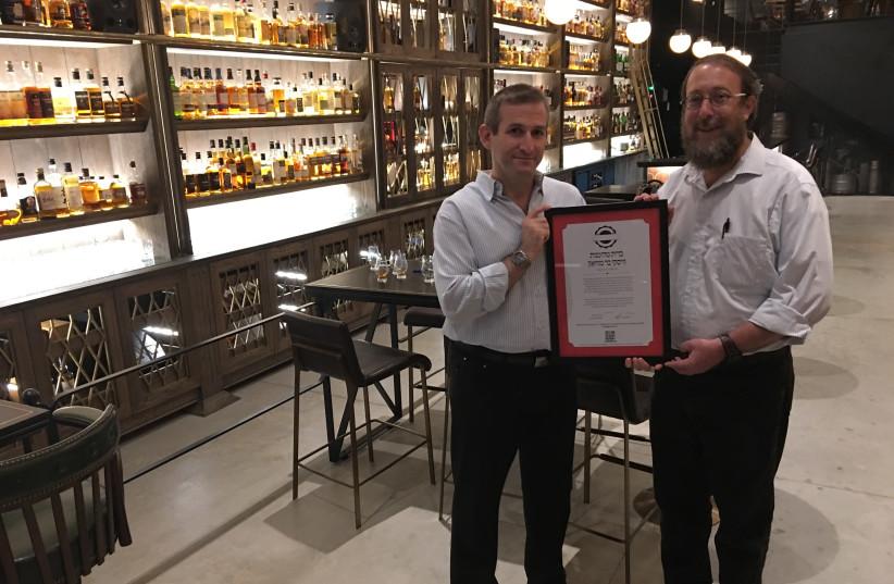 Hashgacha Pratit founder Rabbi Aharon Leibowitz (right) presenting a supervision certificate to the Whisky Bar Museum in Tel Aviv.  (photo credit: HASHGACHA PRATIT)