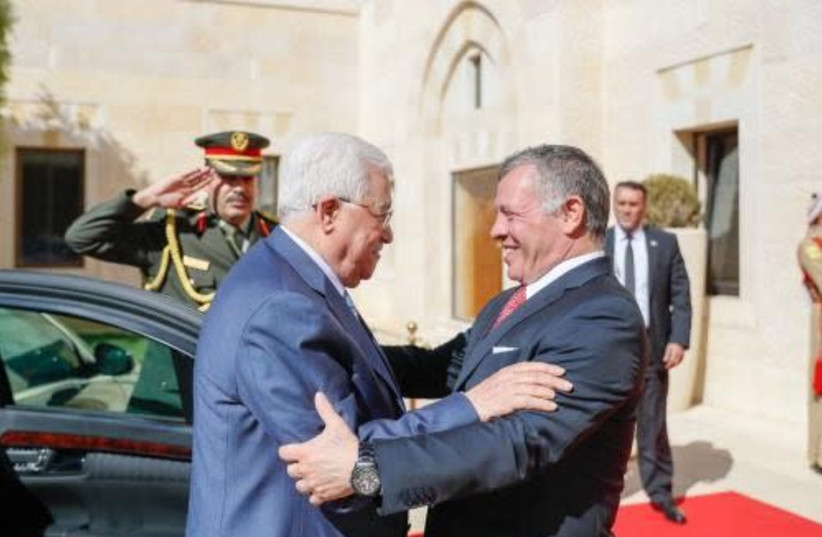 Palestinian Authority President Mahmoud Abbas and Jordanian King Abdullah greet each other in the courtyard of the Husseiniya Palace in Amman, October 22, 2017. (photo credit: WAFA)