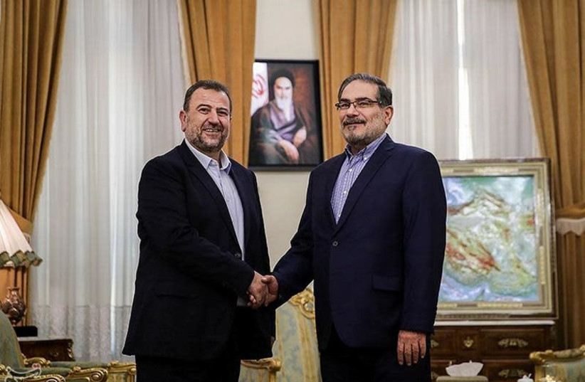 Saleh al-Arouri (L), Hamas deputy chief, shakes hands with Ali Shamkhani, secretary of Iran's National Security Council, during their meeting in Tehran, Iran October 21, 2017. (photo credit: TASNIM NEWS AGENCY/HANDOUT VIA REUTERS)