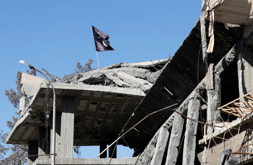 A flag of Islamic State militants is pictured above a destroyed house near the Clock Square in Raqqa (photo credit: ERIC DE CASTRO/ REUTERS)