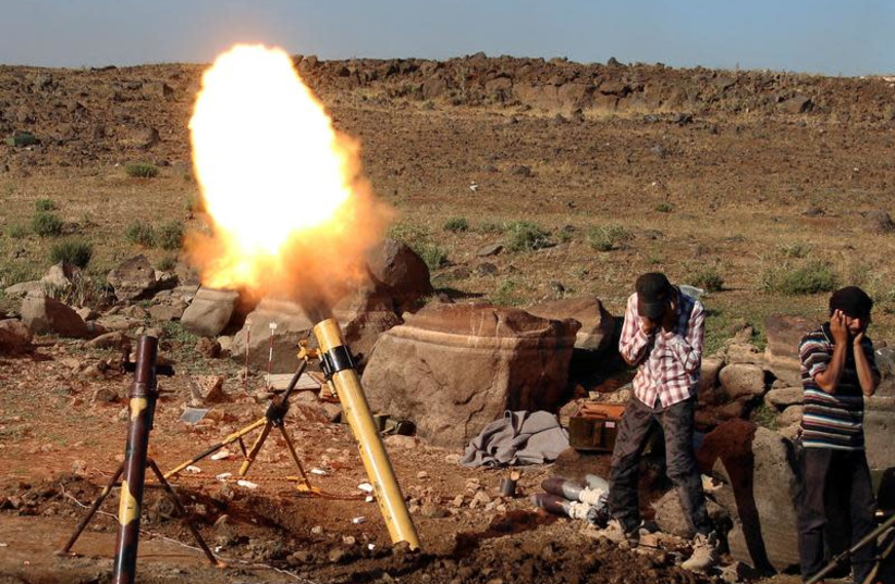Rebel fighters fire mortar shells towards forces loyal to Syria's President Bashar Assad in Quneitra province, bordering the Golan Heights, Syria June 24, 2017. (photo credit: ALAA AL-FAKIR / REUTERS)