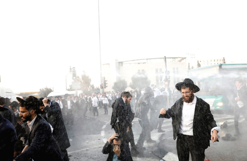 Water-canon spray hits ultra-orthodox protesters during demonstrations in the capital yesterday.  (photo credit: RONEN ZVULUN/REUTERS)