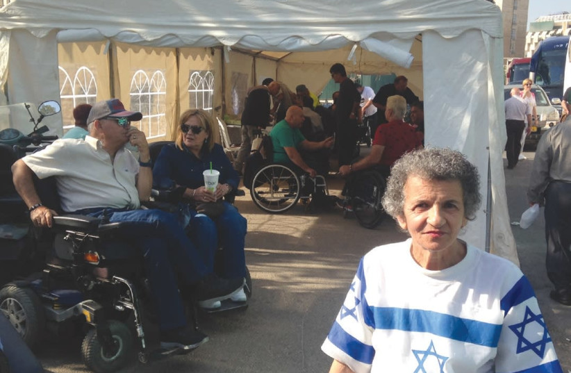 Demonstrators from 15 groups representing people with disabilities gather in their protest tent outside of the Knesset in Jerusalem yesterday. (photo credit: SARAH LEVI)