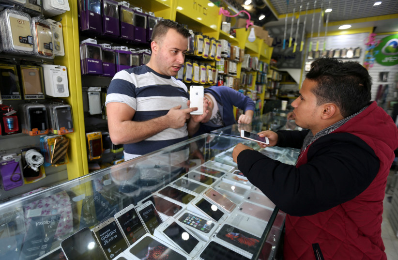 A Palestinian seller shows a smartphone to a customer in a mobile phone shop in Gaza City. (photo credit: REUTERS)