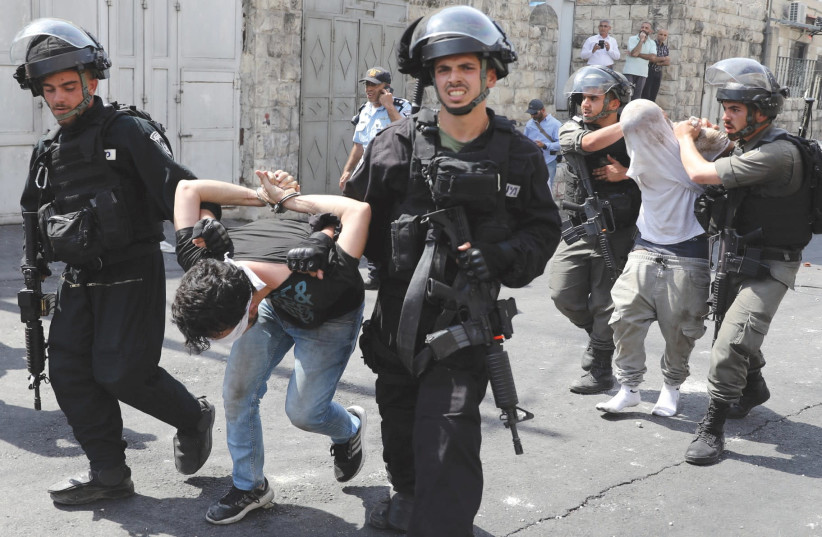 Police arrest Palestinians outside the Old City, July 2017 (photo credit: AMMAR AWAD / REUTERS)