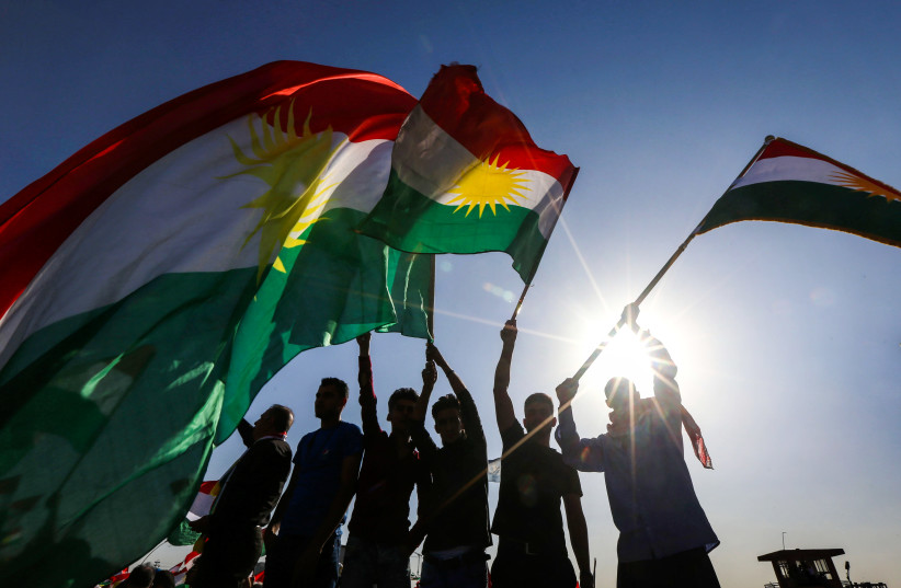 Iraqi Kurds wave flags of Iraqi Kurdistan during a demonstration (photo credit: SAFIN HAMED / AFP)