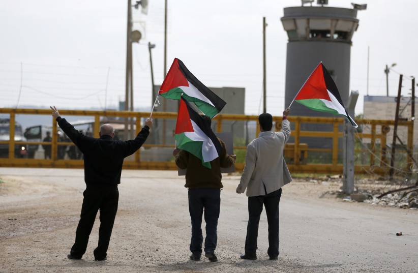 Palestinian protesters wave their national flag outside of an Israeli prison (photo credit: ABBAS MOMANI / AFP)