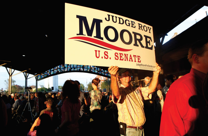 A supporter of US Senate candidate Judge Roy Moore holds a sign as he waits for a campaign rally in Montgomery, Alabama, earlier this year. (photo credit: REUTERS)