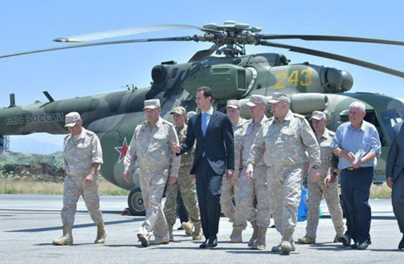 Syria's President Bashar Assad visits a Russian air base at Hmeymim, in western Syria in this handout picture posted on SANA on June 27, 2017, Syria. (photo credit: SANA/HANDOUT VIA REUTERS)