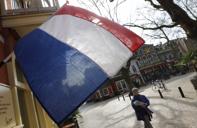 A woman walks past a national flag, the day before a general election, in Delft, Netherlands, March 14, 2017. (photo credit: REUTERS)