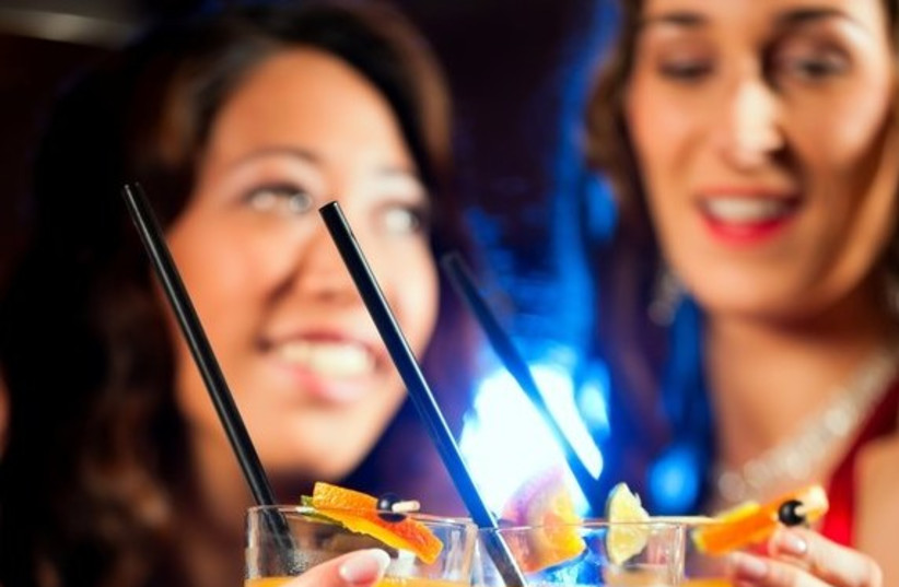 Women drink cocktails at a bar (photo credit: ING IMAGE/ASAP)
