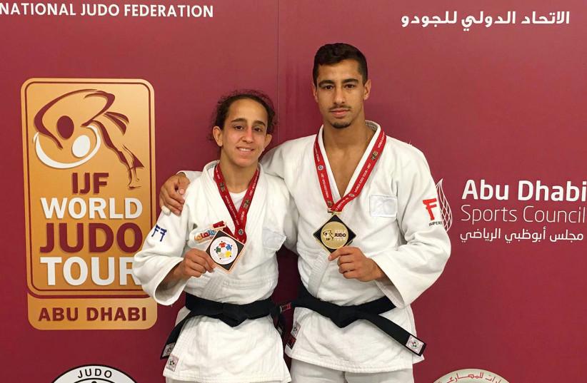Israeli judokas Gili Cohen, winner of the bronze medal in the Women's -52kg, and Tal Flicker, winner of the gold medal in the Men's -66kg category at the Abu Dhabi Judo Grand Slam (photo credit: AFP PHOTO / HO / ISRAEL JUDO FEDERATION)