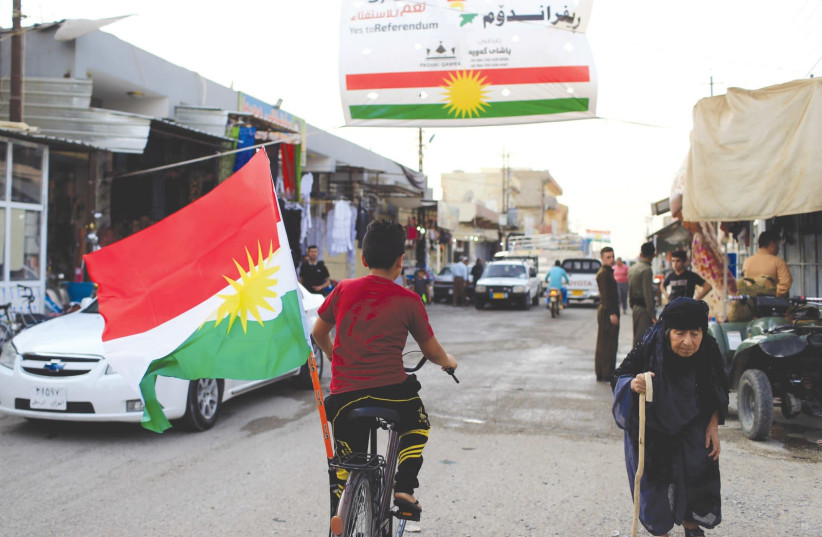A BOY rides a bicycle with the flag of Kurdistan in Tuz Khurmato, Iraq. (photo credit: REUTERS)