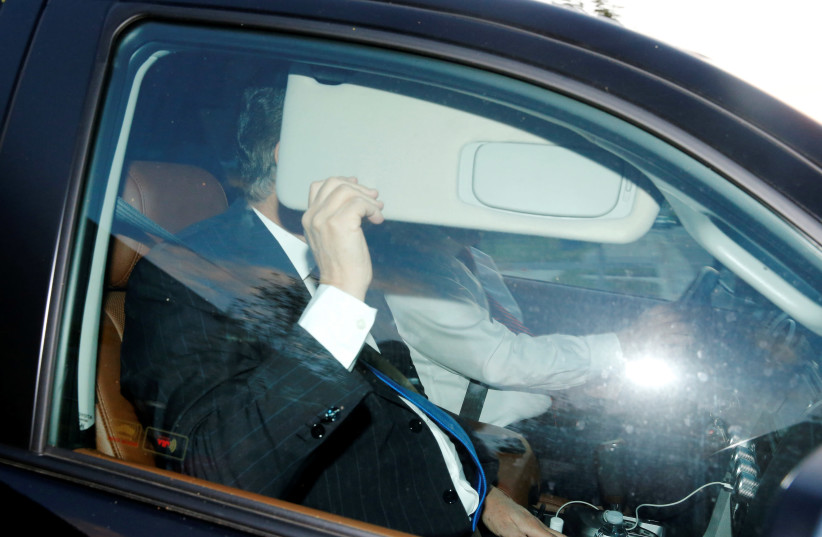 Former Trump campaign manager Paul Manafort hides as he leaves to submit to investigation (photo credit: JONATHAN ERNST / REUTERS)