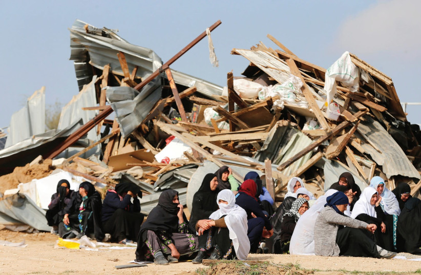 Beduin women sit beside ruins from of their homes in Umm el-Hiran, which was destroyed in January 2017  (photo credit: AMMAR AWAD / REUTERS)