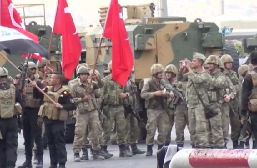 Iraqi and Turkish soldiers wave flags at the Habur Border Gate between Turkey and Iraq (photo credit: IHA/ VIA REUTERS)