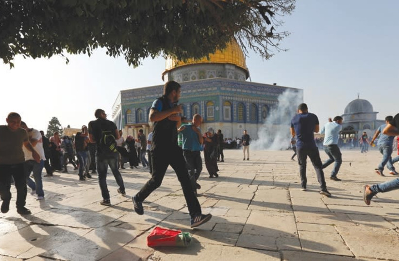 Palestinians react as stun grenades explode on the Temple Mount in Jerusalem's Old City during riots at the site on July 27. (photo credit: REUTERS/MUAMMAR AWAD)