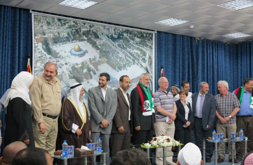 PSC Chairman Hugh Lanning (second from the right) standing with Hamas Cheif Ismail Haniyeh (center). (photo credit: COURTESY MINISTRY OF STRATEGIC AFFAIRS)