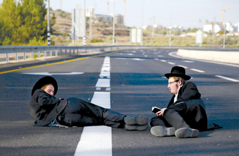 ULTRA-ORTHODOX men sit on a road during the 'day of rage' protest near Modi'in on October 19 (photo credit: AMMAR AWAD/REUTERS)