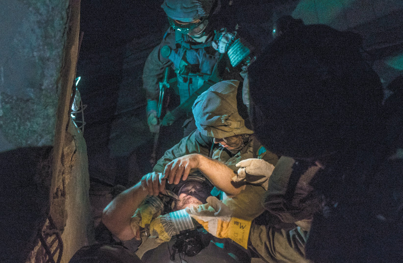 THE WRITER being 'rescued' by members of the Search-and-Rescue Unit (photo credit: IDF SPOKESPERSON'S UNIT)