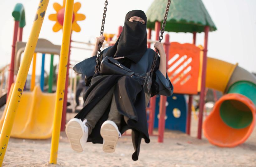 A Saudi woman swings at a park in Jeddah (photo credit: REUTERS/REEM BAESHEN)