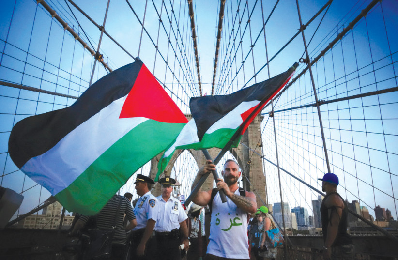 A MAN holds two flags as demonstrators at a 2014 pro-Palestinian rally march across the Brooklyn Bridge in New York City (photo credit: REUTERS/EDUARDO MUNOZ)