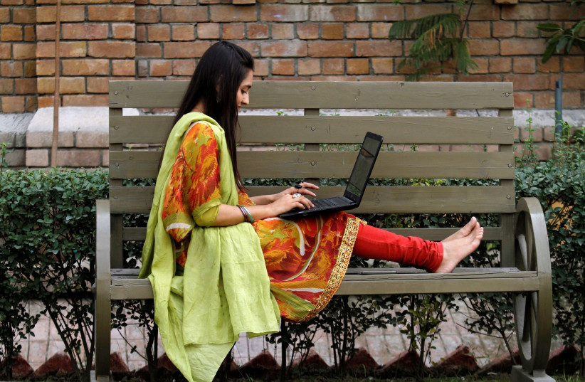 A student works on her computer sitting on a bench at Shaheed Benazir Bhutto Women's University in Peshawar, Pakistan  (photo credit: REUTERS/ FAYAZ AZIZ)