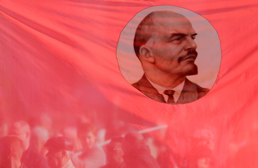 Russians hold up a flag emblazoned with Communist leader Vladimir Lenin (photo credit: EDUARD KORNIYENKO)