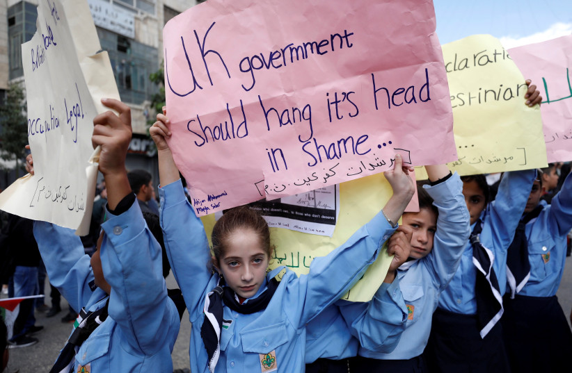 Palestinian children hold signs protesting the UK's acknowledgment and celebration of the Balfour Declaration cenetennial in mass protests.  (photo credit: MOHAMAD TOROKMAN/REUTERS)