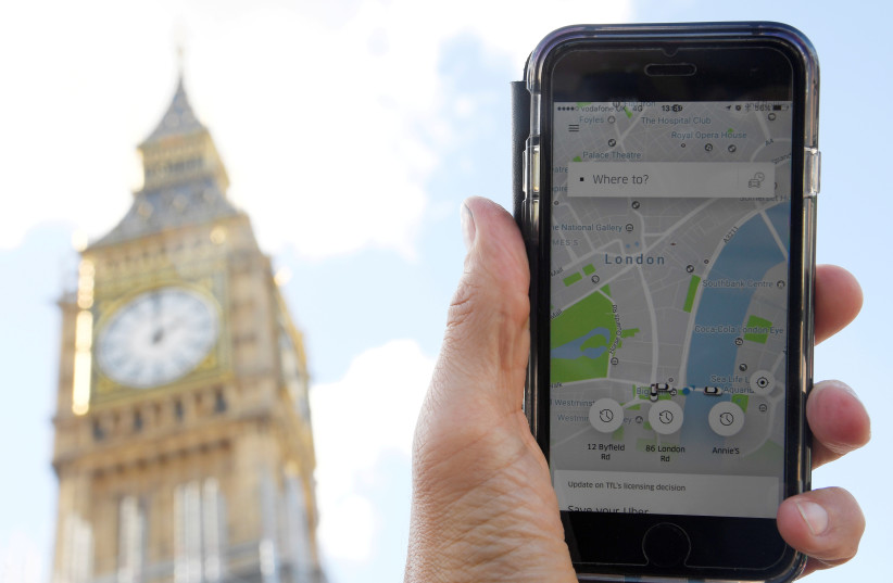 A photo illustration shows the Uber app on a mobile telephone, as it is held up for a posed photograph in central London, Britain September 22, 2017. (photo credit: REUTERS)