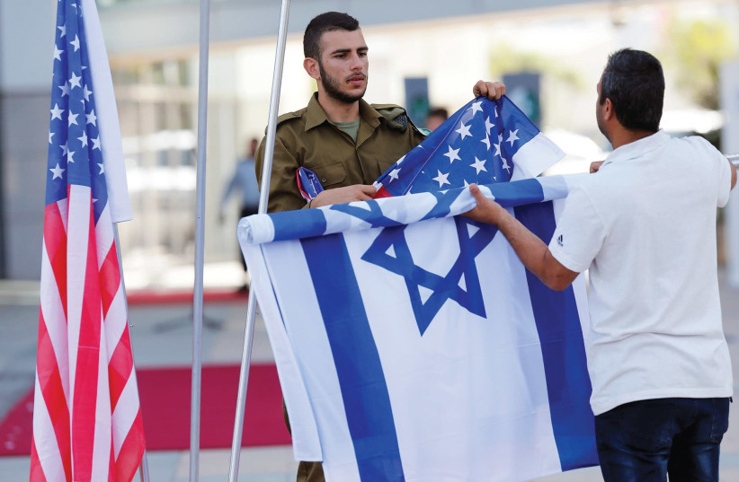 An Israeli soldier arranges Israeli and American flags (photo credit: REUTERS)