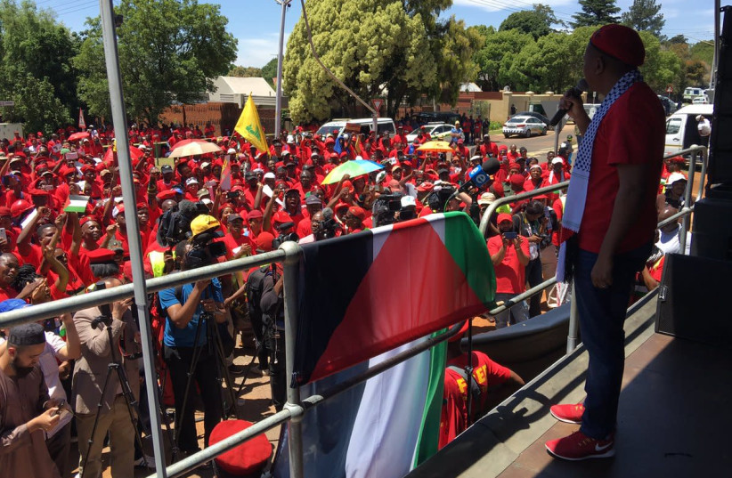 EFF leader Julius Malema addresses anti-Israel protesters on Thursday as a Hezbollah flag flies in the background, outside the Israeli Embassy in South Africa (photo credit: COURTESY TWITTER)