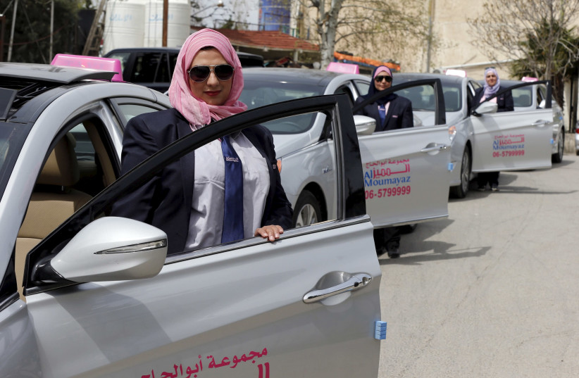 Female taxi drivers pose for a photo in front of their vehicles at Noor Jordan for Transport — Taxi Moumayaz's (Special Taxi) parking lot in Amman, Jordan, March 24, 2016. (photo credit: MUHAMMAD HAMED / REUTERS)