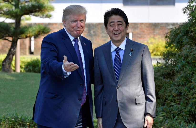 US President Donald Trump (L) gestures with Japanese Prime Minister Shinzo Abe upon his arrival at the Kasumigaseki Country Club in Kawagoe, near Tokyo, Japan, 05 November 2017 (photo credit: REUTERS/FRANK ROBICHON/POOL)