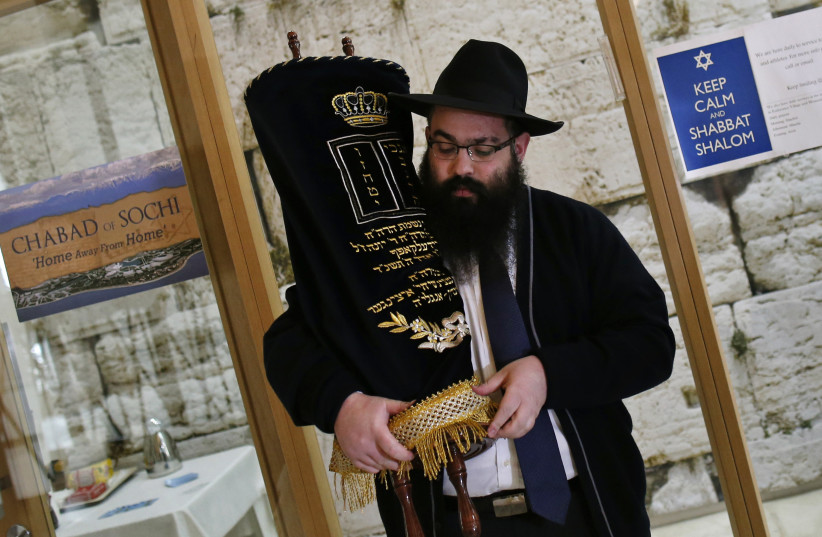 Rabbi Ari Edelkopf holds a Torah scroll at one of several prayer centers set up to cater to Jewish visitors to the 2014 Sochi Winter Olympic Games in Russia. (photo credit: REUTERS/MIKE SEGAR)