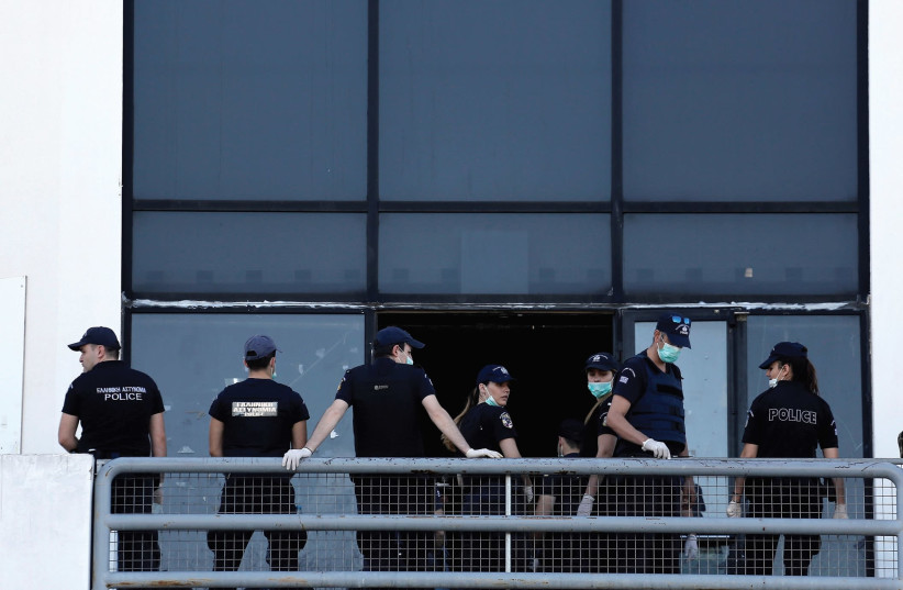 POLICE OFFICERS stand guard at the entrance of the disused Hellenikon airport during a police operation to clear out a makeshift migrant camp in Athens. (photo credit: REUTERS)