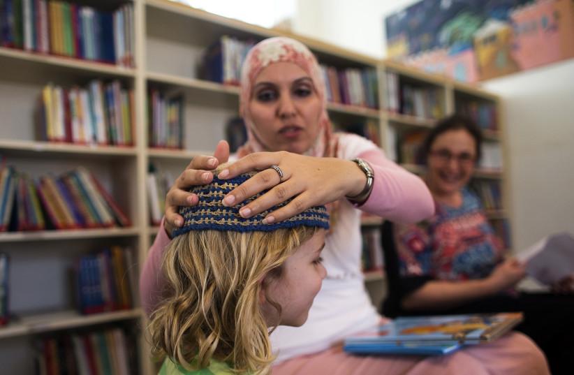 Alia Tunisi, a school teacher, and one of her students at Jerusalem's Hand in Hand Arab-Jewish bilingual school. (photo credit: RONEN ZVULUN / REUTERS)