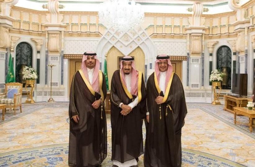 Saudi King Salman bin Abdulaziz Al Saud poses for a photo with National Guard Minister Khaled bin Ayyaf and Economy Minister Mohammed al-Tuwaijri during a swearing-in ceremony in Riyadh, Saudi Arabia, November 6, 2017.  (photo credit: SAUDI PRESS AGENCY/HANDOUT VIA REUTERS)